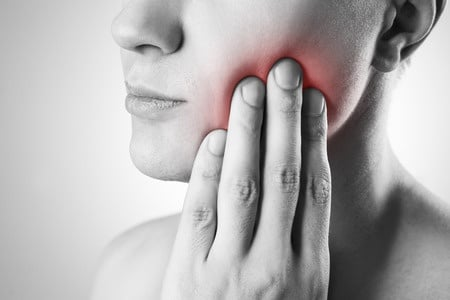 Person holding cheek in pain from tooth or wisdom tooth